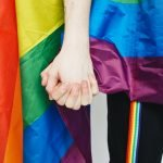 people with a gay pride flag holfing hands